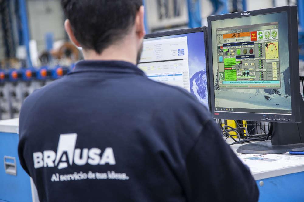 Foto operario técnico con máquina de producción de perfiles de acero conformados en frío de Brausa